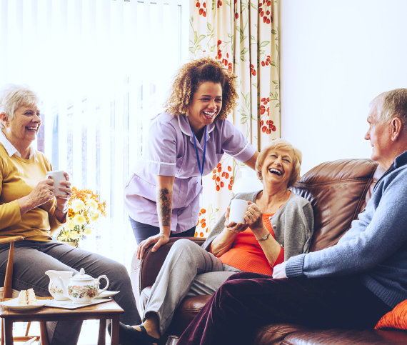 a group of seniors laughing with their caregiver