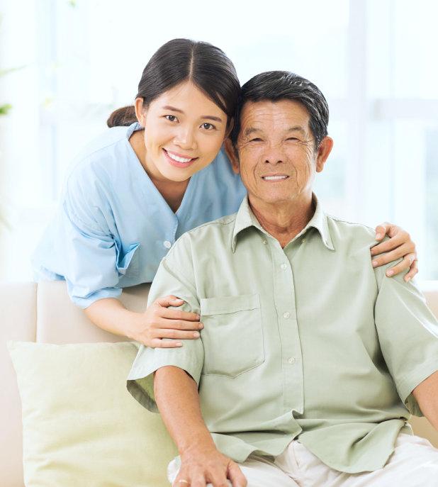 a caregiver and a senior man smiling