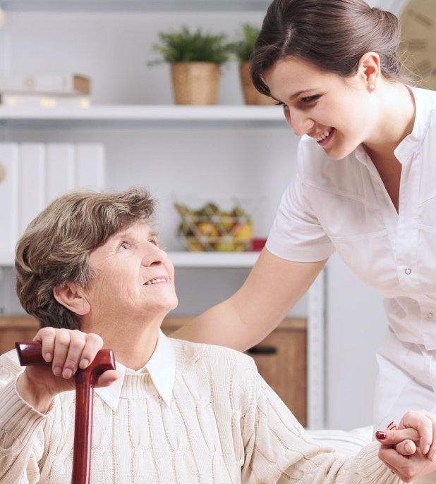 a caregiver and a senior woman looking at each other while smiling