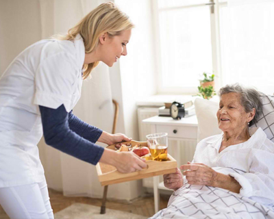 a caregiver serving meal for the senior woman in bed