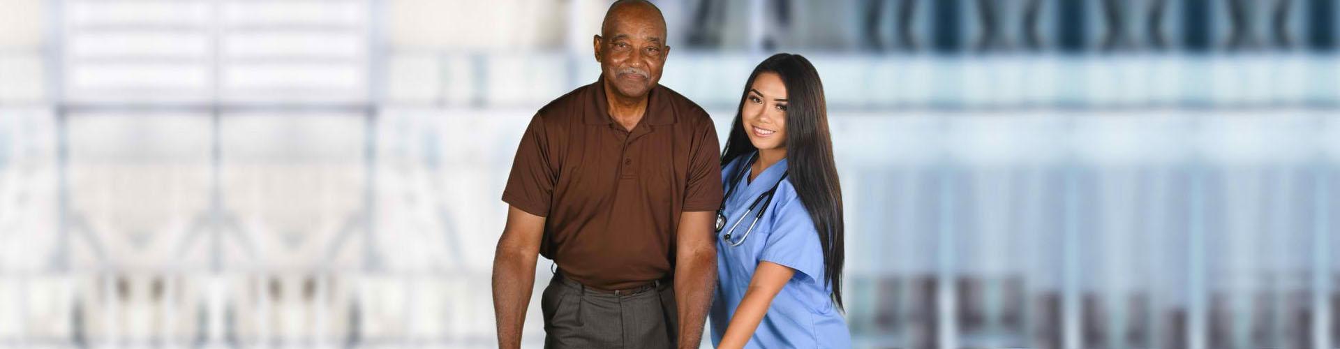 a nurse assisting a senior man walk
